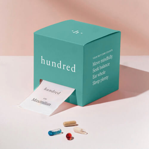 A Hundred vitamin box with a daily pack coming out of its front opening